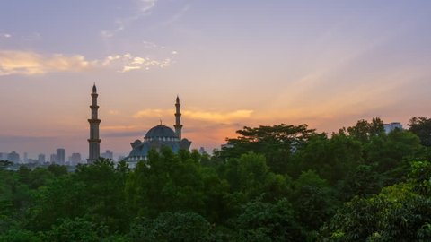 Time lapse. Sunrise at Federal Territory Mosque in Kuala Lumpur with silhouette city skyline in the background.