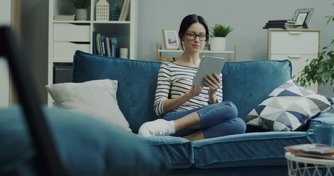 Caucasian young good looking woman in glasses using tablet device and thinking while sitting on the blue sofa at home.