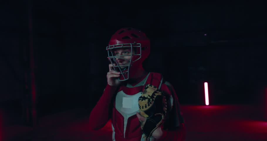 ORBITAL SHOT Caucasian professional baseball player catcher posing against dark background. 4K UHD 60 FPS SLOW MOTION #1026481460