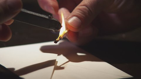 Hand close up melting wax onto a letter. Sealing a letter the old fashioned way