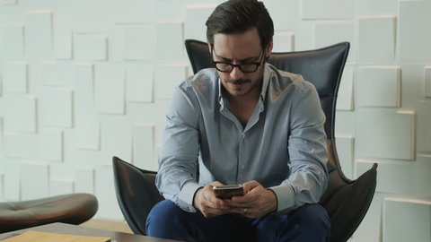 Happy business man relaxing with cell phone at work in office, busy hispanic boss working and typing text message on mobile telephone. Businessman smiling, worker as latino manager in waiting room