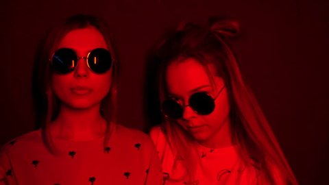 Fashion portrait of two young girls in sunglasses. Beautiful hipster women posing in red neon light. Sexy model exhaling smoke from electronic cigarette. Vaporizer shot in slow motion. 4k