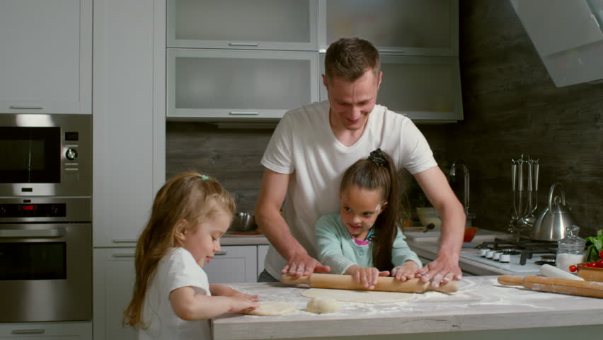 Medium shot of father and two daughters making dough together in kitchen, man teaching one of girls to use rolling pin | Shutterstock HD Video #1026621680