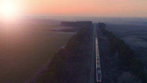 Aerial following view of a high-speed train moving fast on the countryside at sunset