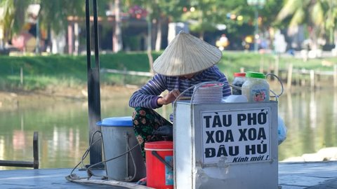 Hoi An, Vietnam - 11 2018: Stock footage of Vietnamese vendor on the road in Hoi An old town. Women with conical hat selling street food for tourist. Hoi An is one of the most popular destinations