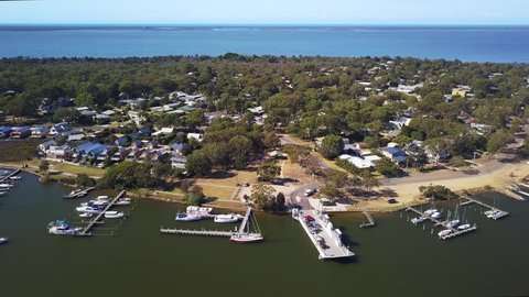 An aerial view of Raymond Island, Australia showing the coastline, piers, and moored boats.