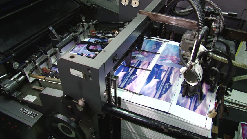 Pages being fed into a two color offset printing press. All the photographic images in this clip are property released.
