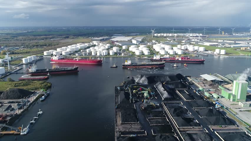 Aerial arriving at of busy harbor area oil depot is an industrial facility for storage of petrochemical products showing tankers and tugs maneuvering the congested port waters 4k high resolution | Shutterstock HD Video #1026763790