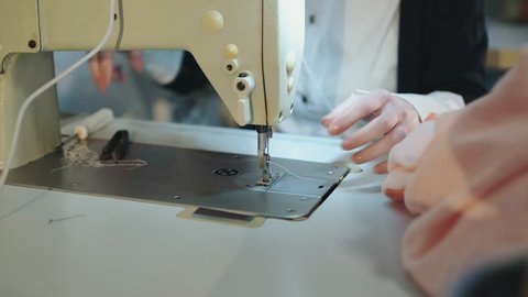 Close view of sewing the stitching on cloth with sewing machine. 4K