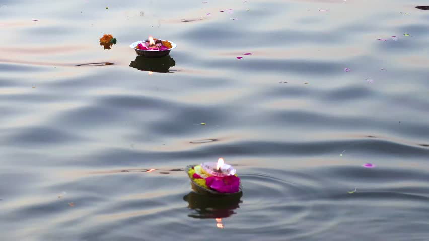 Hinduism religious ceremony puja flowers and candle on the sacred river Ganges water in Varanasi, India, close up, 4k footage video