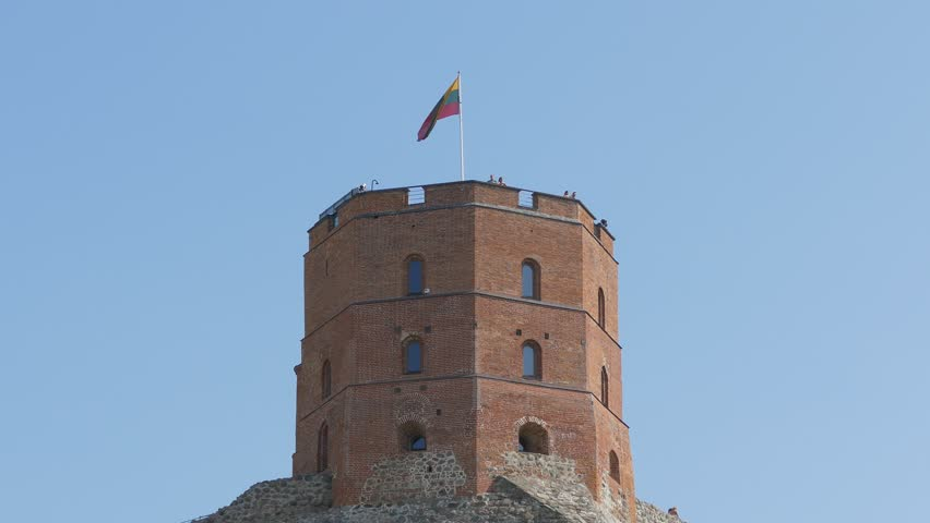 Ungraded: National flag of Lithuania flies over the Gediminas' tower. Unrecognizable tourists look at the city from the tower. Ungraded H.264 from camera without re-encoding.   Shutterstock HD Video #1026818480