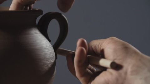 Man hands making clay product. Potter make jug handle from clay in slow motion. Close up of potter's work.