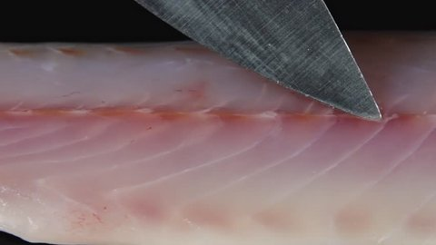 The fillet of fish lies on a black background. The knife slowly moves along the entire piece. Fillet of fish lies on a dark background. Food video.