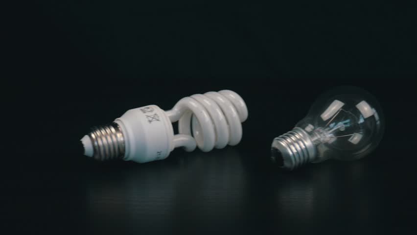 Two diffrent light bulbs on black table. Camera moves from right to left | Shutterstock HD Video #1026870140