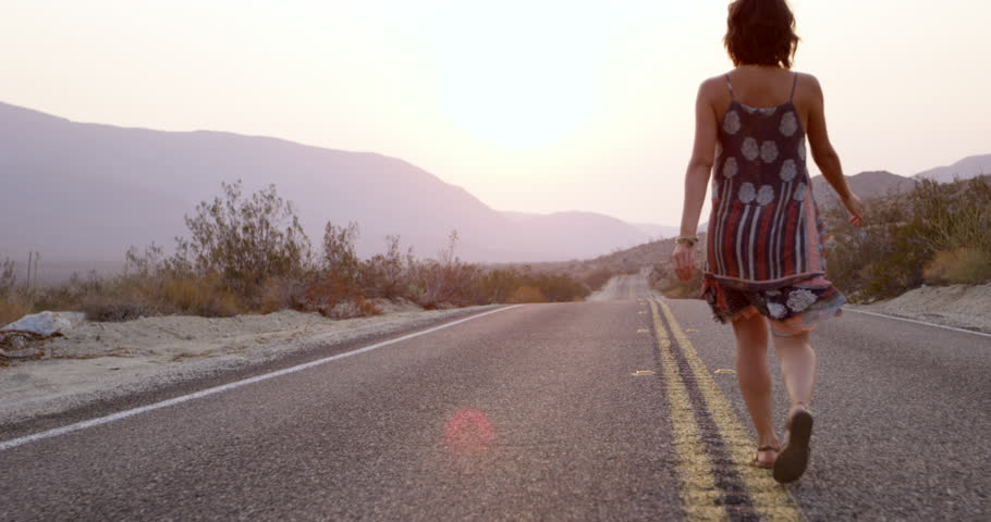 Young stylish woman walks down center of desert highway -wide shot - young hippy adventure | Shutterstock HD Video #1026889640