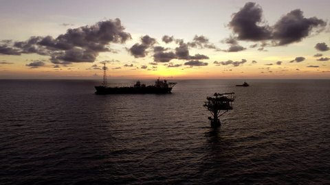 Aerial view Silhouette of oil production platform or oil rig with supply vessel during sunset at oil field
