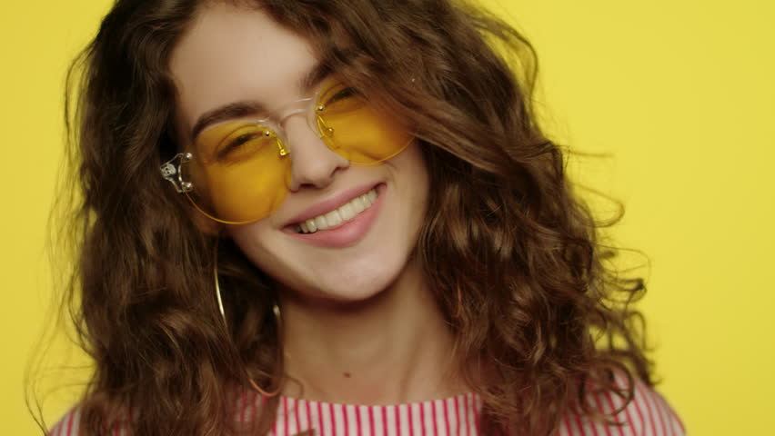 Young woman smiling on yellow background. Portrait of happy girl smiling in studio. Close up of fashion model smile. Happy woman in yellow sunglasses looking in camera #1026902270