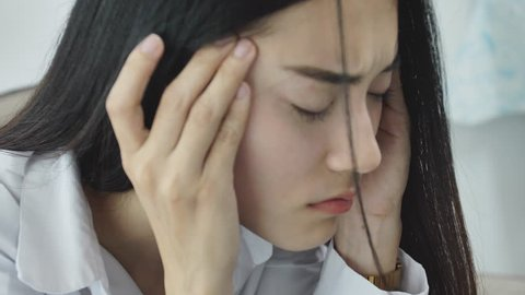 Asian woman feeling stress from work in the office.Tired business woman at workplace in office holding his head on hands feel headache.