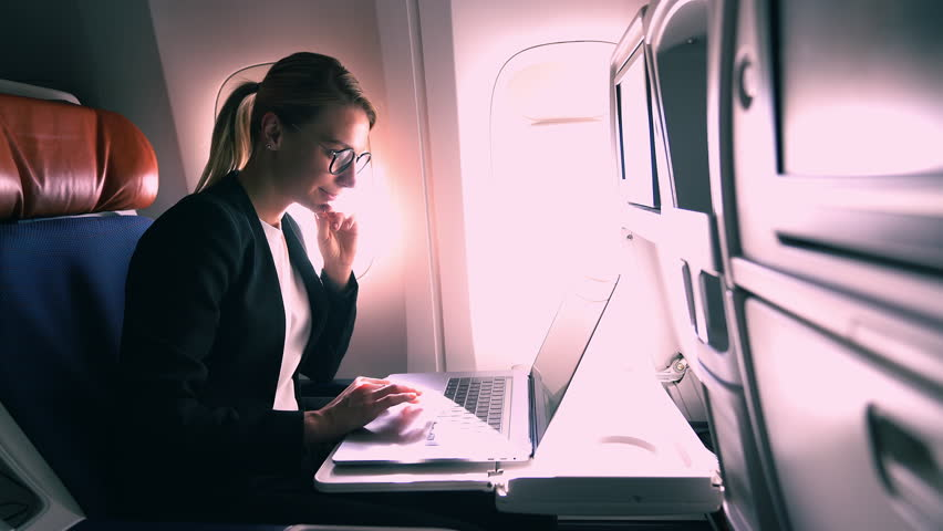 Successful young entrepreneur working online on freelance in flight.Female aircraft passenger keyboarding email on laptop computer while flying on board of modern airline with Wireless Internet access | Shutterstock HD Video #1026966530