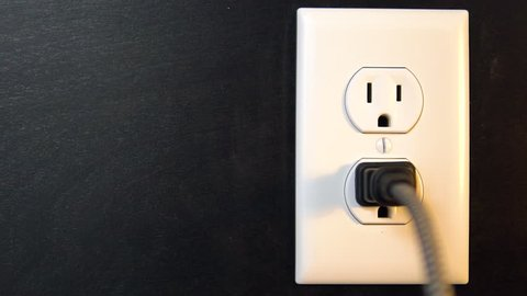 Lights on and off when a two pronged cord connects and disconnects with the bottom outlet of an American electrical socket, Copy Space Left