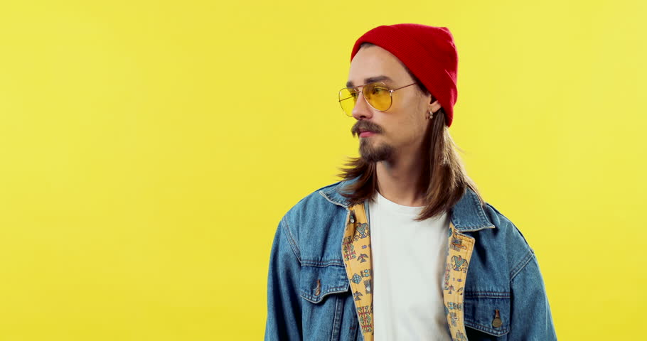 Portrait of the Caucasian handsome young guy in hipster style, sunglasses and hat smiling to the camera on the yellow background. | Shutterstock HD Video #1027041500