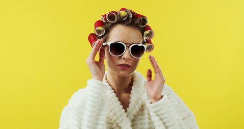 Portrait shot of the funny Caucasian young lady in the sunglasses, curlers and bathrobe coming in front of the camera, looking at herself like in the mirror and going away on the yellow wall