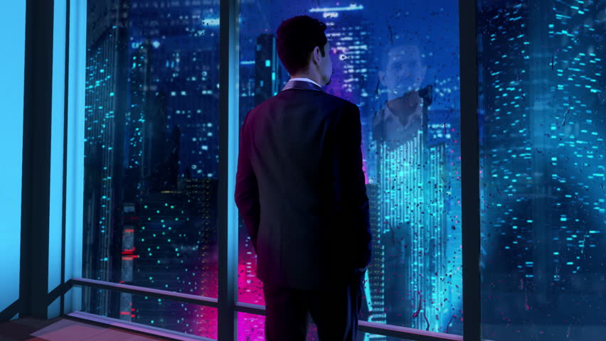 In the near future, thoughtful Businessman wearing a suit standing in his office, looking out of the window and staring at a futuristic city with skyscrapers and colorful lights.   Shutterstock HD Video #1027051820