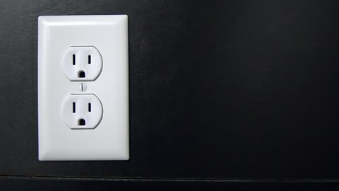 Male hand plugs in and unplugs a two pronged cord into the bottom outlet of an American electrical socket, Copy Space Right