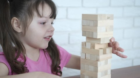 Board game. Happy little girl pulls wooden blocks.