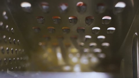 Closeup of rubbing the cheese on metal grater