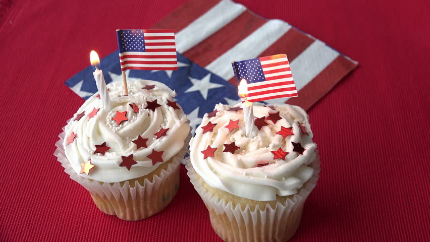 a62d842c4ba Two patriotic birthday cupcakes with burning candles and tiny American flags.  The background is red with a flag napkin. Red stars are on the vanilla  frosted ...