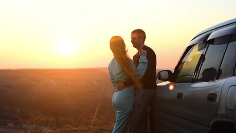 couple girl and boy hugging at sunset. standing near the car. love story