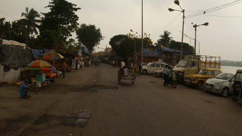 Kolkata / West Bengal, India - september 23, 2018 : POV man walk on street of Kolkata market raws cycle rickshaw river old buildings