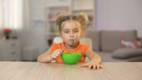 Hungry female kid eating cornflakes with milk and showing thumbs up, breakfast