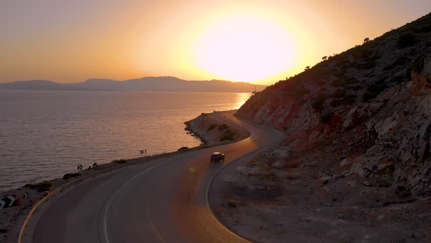 AERIAL: Flying along an empty coastal road on a serene summer evening leading around the picturesque Greek island. Car exploring the breathtaking sights of the Mediterranean sea and scenic Lefkada. | Shutterstock HD Video #1027340810