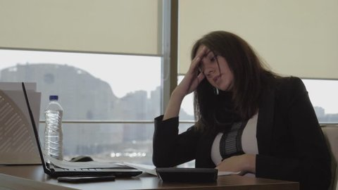 Tired pregnant caucasian woman secretary in business suit working at the workplace in office, leans back in chair, drinking water from a plastic bottle, then stroking her hand stomach, slow motion