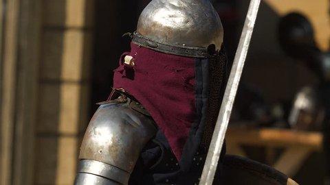 Warrior in a worn armor dodging rival strikes