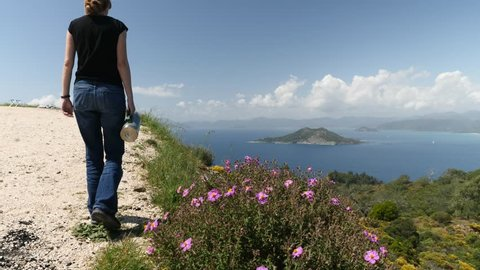 lady watching the sea and island on the hill with clouds holding a thermos flask