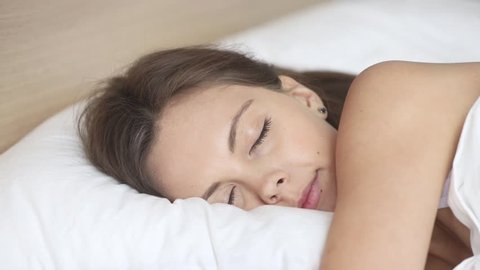 Calm young woman sleeping well in comfortable cozy fresh bed on soft pillow white linen orthopedic mattress, peaceful serene girl resting lying asleep enjoying healthy good sleep nap in the morning
