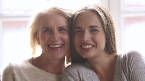 Happy beautiful loving family old mature mother and adult daughter laughing bonding looking at camera, smiling senior mom with young woman having fun enjoy connection and warm relationships, portrait