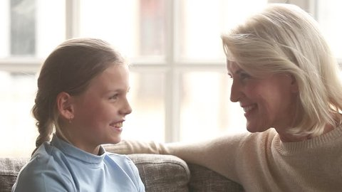 Loving old grandma psychologist and cute little child granddaughter talking having fun trust conversation sitting on sofa, kid girl grandchild chatting with grandmother at home enjoy time together