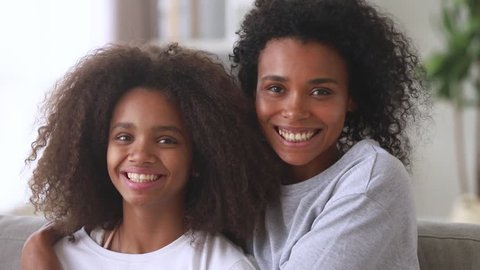 Happy african american family mom with teen daughter hugging laughing looking at camera, cheerful black mother embracing child teenage girl cuddling having fun feeling love and bonding, portrait