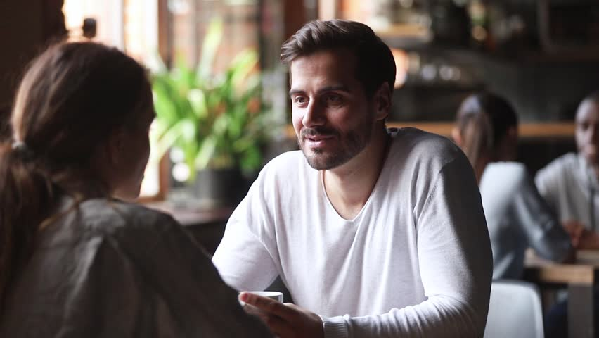 Young man having serious and friendly conversation with woman girlfriend sit at cafe table drinking coffee, male female friends colleagues talking chatting discussing work at meeting in coffeehouse | Shutterstock HD Video #1027488650
