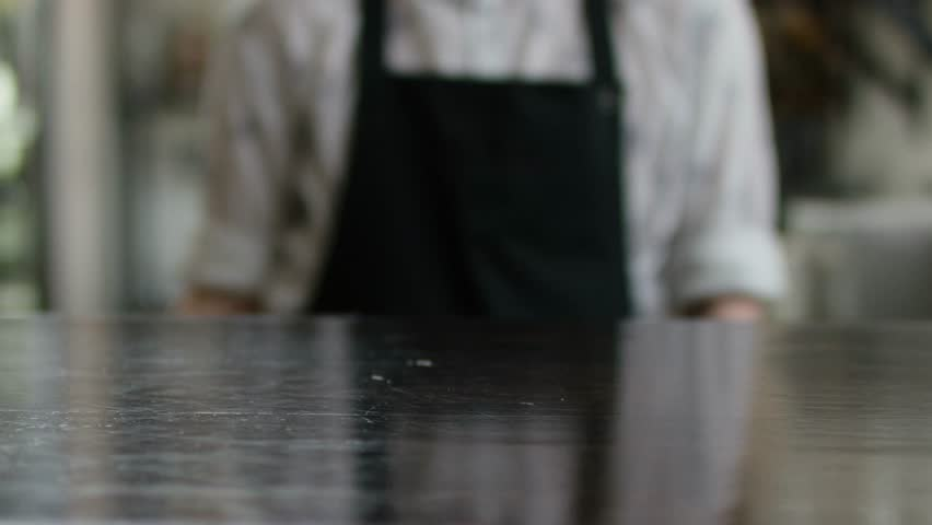 A strong waiters hand carries a brown tray with a glass of coctail to the customers. Modern cafe. Morning traditions. Cafe settings, wooden furniture on the background. putting a glass on th table | Shutterstock HD Video #1027523390