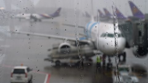 Storm at the airport. View of the airplane through rain drops and streams. Themes of weather and delay or canceled flight.