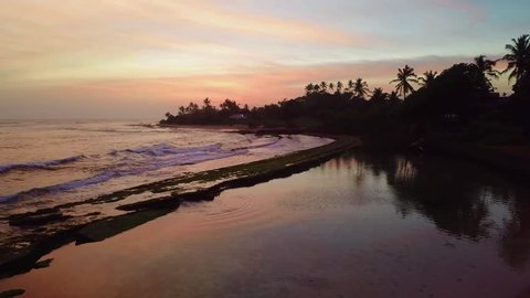 Colorfull Sunset with waves crushing into the sand - Paradise