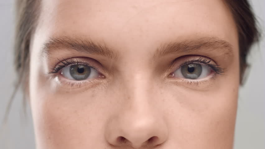 Extreme close-up of young brown-haired freckled Caucasian woman opening her eyes in front of camera against a grey background | Shutterstock HD Video #1027606640