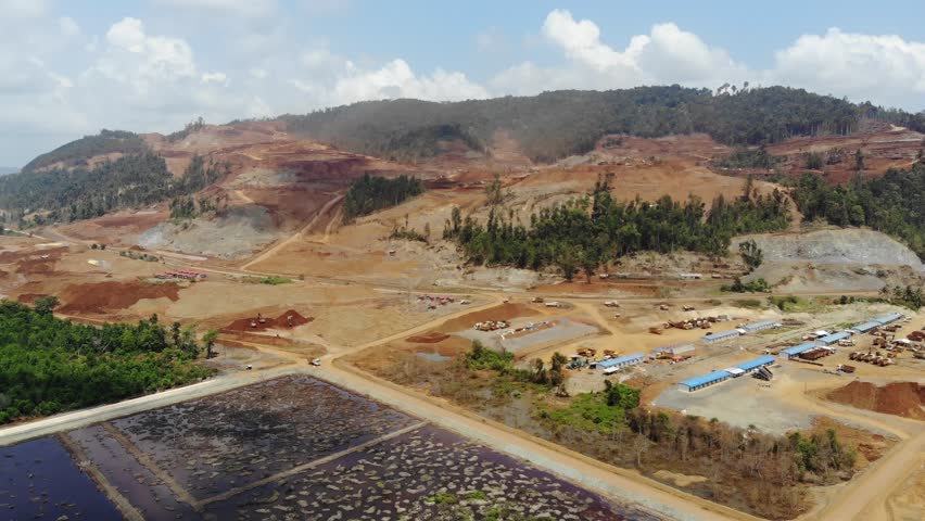 Aerial view of mining and deforestation in the Philippines. Heavy equipment clearing a mountainside ring all trees and foliage. Industrialization of a tropical paradise and environmental impact.