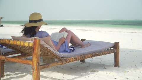 Young woman is reading book on white sand beach by ocean. Adult caucasian girl in straw hat and sundress is lying on lounger sunbed in shadow on white sandy beach and reading book at bright sunny day.