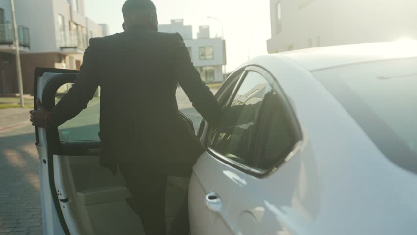 At sunset african american man opens the door of a white car and sits behind the wheel young vehicle open passenger arm auto street automobile businessman buy jacket close up slow motion